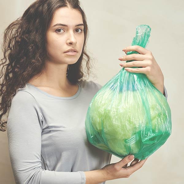Junge Frau schaut in die Kamera und hält einen Müllsack hoch