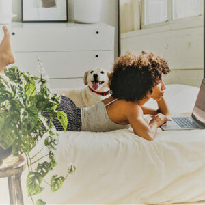 Eine schwarze Frau liegt auf dem Bett und schaut auf ihr Laptop