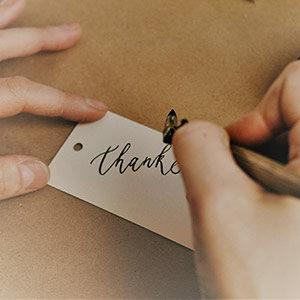 EIne lonke Frauenhnd hält einen Zettel fest, während die rechte Hand das Wort Thanks schreibt