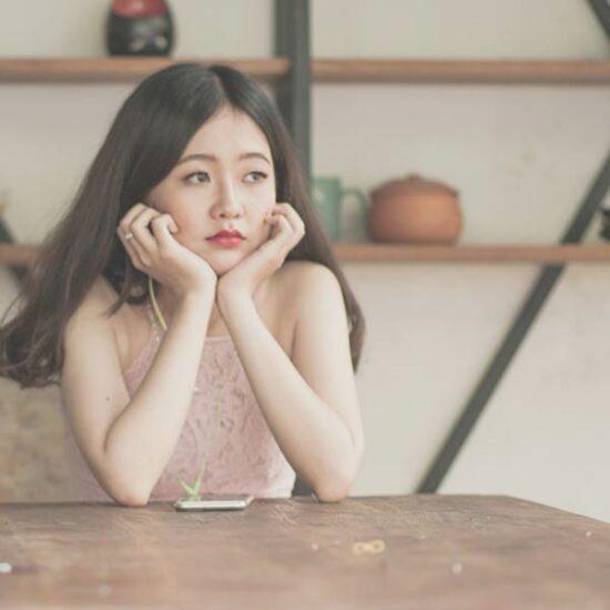 Asiatische junge Frau sitzt an einem Tisch mit Kopfhörern im Ohr und sieht gelangweilt aus