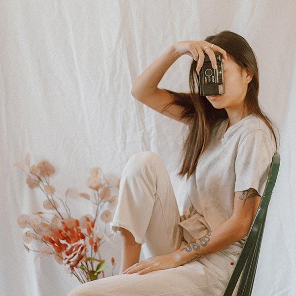 Spirituelle Lebensbegleitung: Junge Frau sitzt auf einem Stuhl und hält sich eine Kamera vor das Gesicht