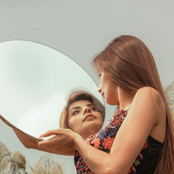 Spirituelle Lebensbegleitung: Junge Frau hält einen Spiegel und schaut hinen