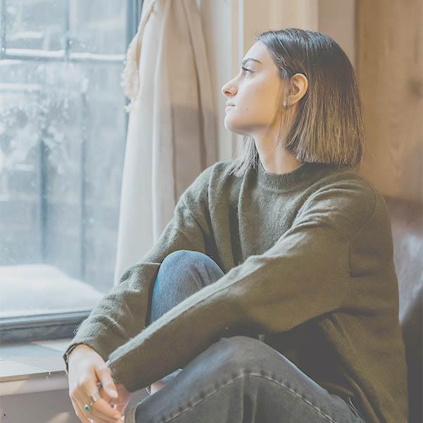 Online-Therapie: Junge Frau sitzt am Fester und schaut melancholisch hinaus