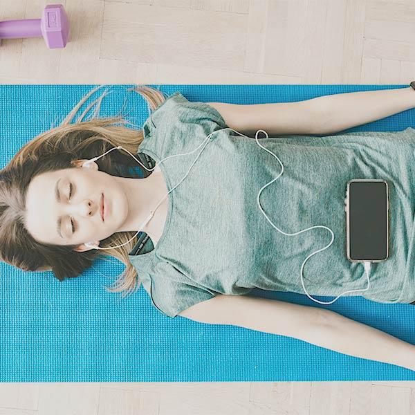 Online-Therapie: Junde Frau liegt mit geschlossenen Augen auf einer Yoga-Matte und hat Kopfhörer in den Ohren