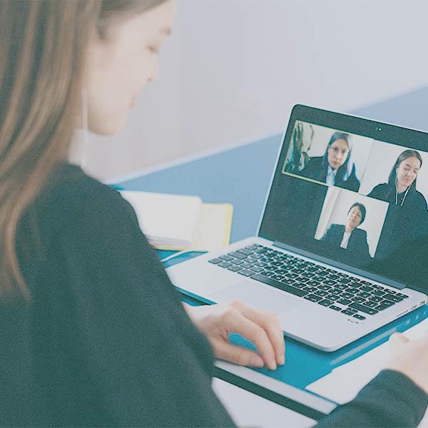 Online-Therapie: Junge Frau sitzt vor enem Laptop, auf dem eine Video-KOnferenz mit mehreren Personen zu sehen ist