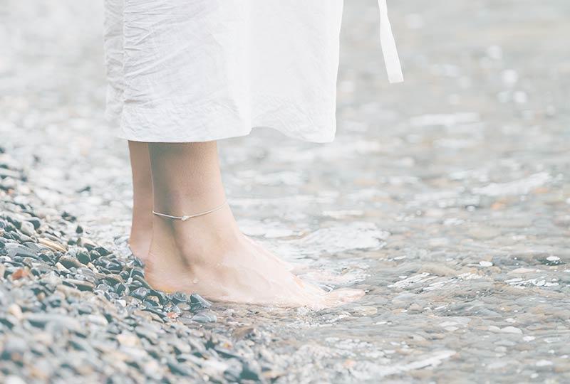 Seminare für Frauen: Füße auf einem Kiesstrand