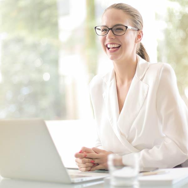 Seminare für Frauen: Frau sitzt am Rehcner und lacht