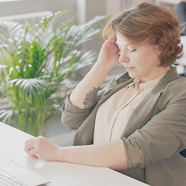 Seminare für Frauen: Frau sitzt am Rechner und hält sich den Kopf
